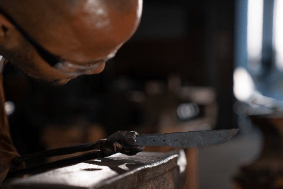 Hold metal in tongs to hammer it into something unique at lawless forge seattle